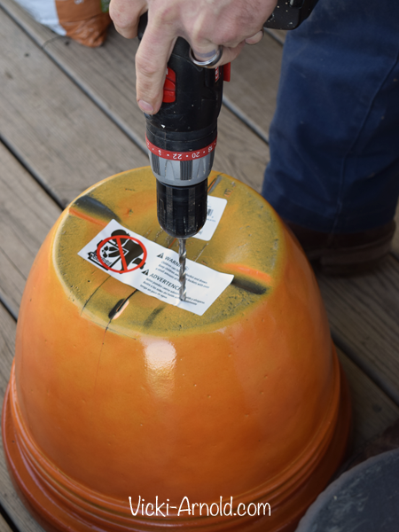 Drilling drainage holes in a container for planting. | Vicki-Arnold.com